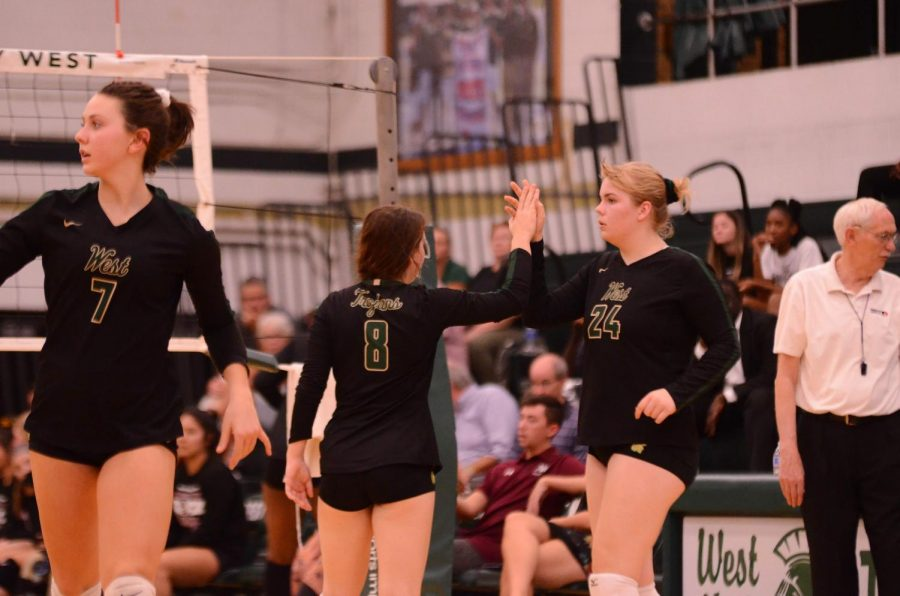 Setters Kearsten Lenth '22 and Emma Dunlap '22 encourage their teammates after scoring a point against Waterloo West on Sept. 29.