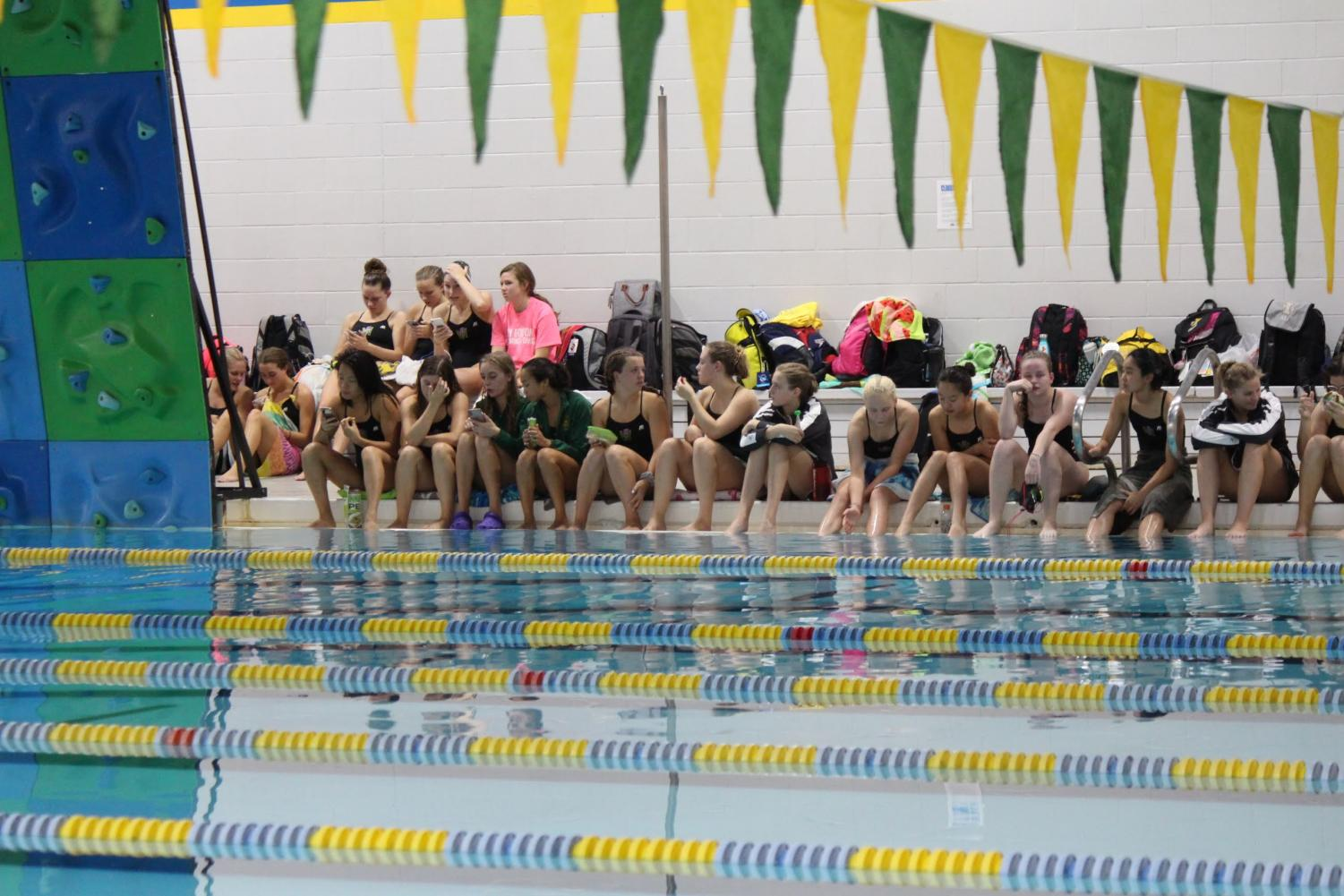 Members of the West High swim team sit as a team to watch the diving portion of the meet on Sept. 17, 2019.