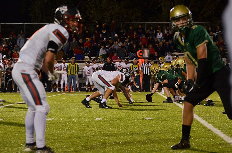 Tate Crane '20 lines up before the offense runs a play against Linn-Mar at the homecoming game at Trojan Field on Oct. 4.