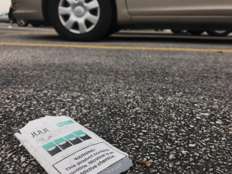 A pack of mint Juul pods sits discarded in the parking lot in front of West.