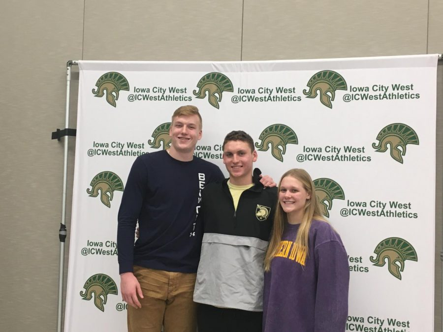 West High senior athletes Even Brauns, James Pinter and Lily Ernst pose for a photo in their school's colors on the fall sports signing day, Nov. 13.