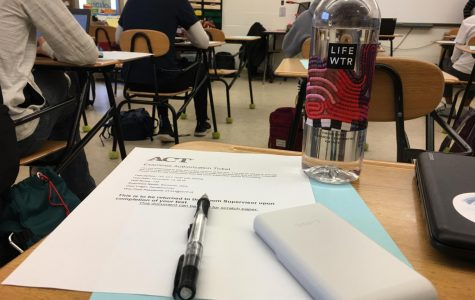 A student's desk sits ready for the ACT, equipped with a pencil, calculator and water bottle.