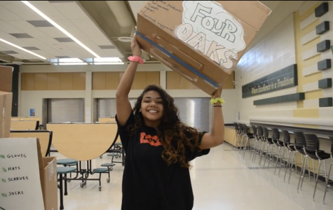 Sabrina Williams '22, iJAG Community Service Representative, poses with one of the donation boxes that can be found around West.