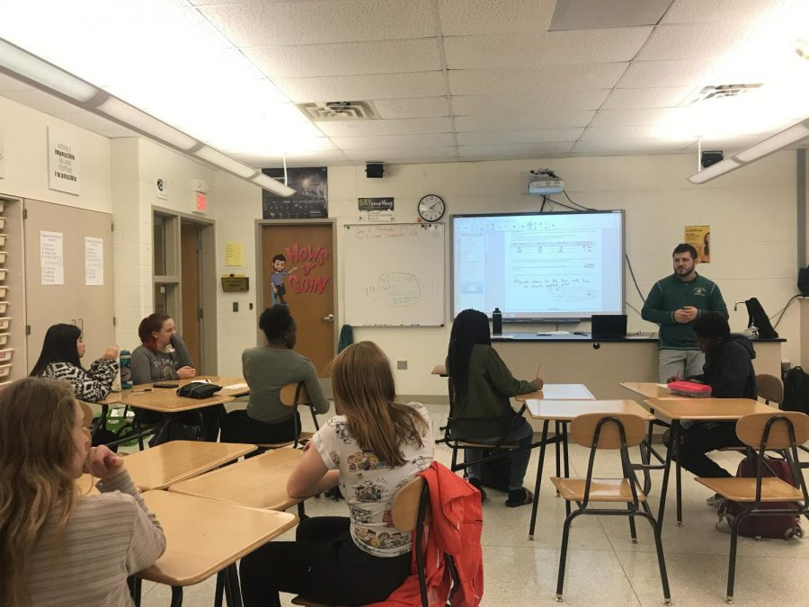 Assistant boys wrestling coach Kody Pudil speaks to a group of about 10 girls after school about uniforms, coaching and the season.