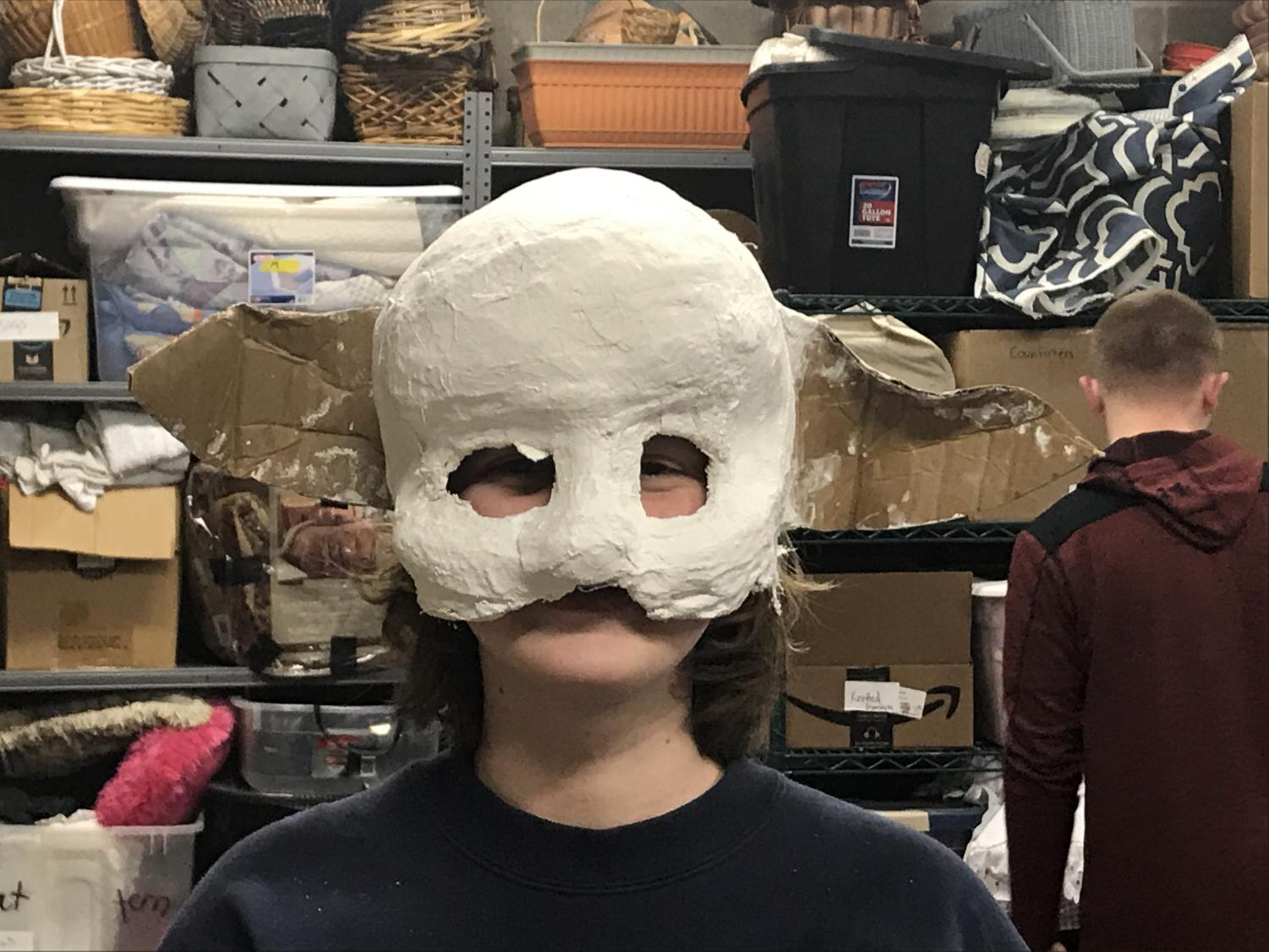 Kaylee Gibson 23' models a monster mask to insure a correct fit before an after school props meeting.