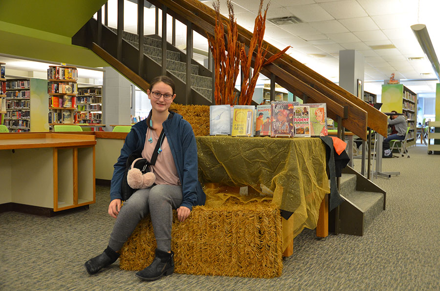 Renee Gould '22 sitting next to the library display.