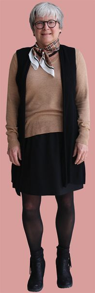 Walker wears a brown sweater paired with a black cardigan and skirt for her second outfit of the week.