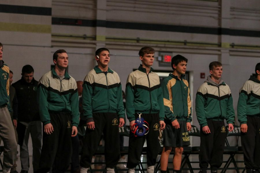 Varsity+wrestlers+stand+during+lineup+introductions+before+the+team%27s+home+opener+against+Dubuque+Hempstead+on+Dec.+12.