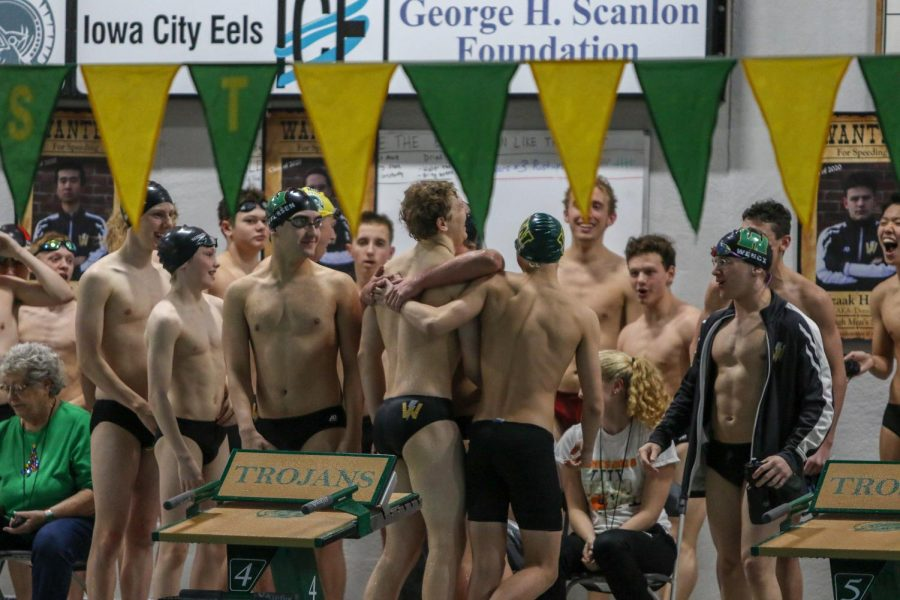 Jordan Christensen '22 is congratulated by his teammates after breaking the 100-yard breaststroke school record in a time of 58.97 seconds during a dual swim meet against Linn-Mar on Dec. 17.