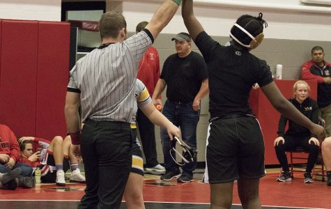 Mayowa Dokun '22 is exhausted, but holds her hand up in victory after her first win of her wrestling career.