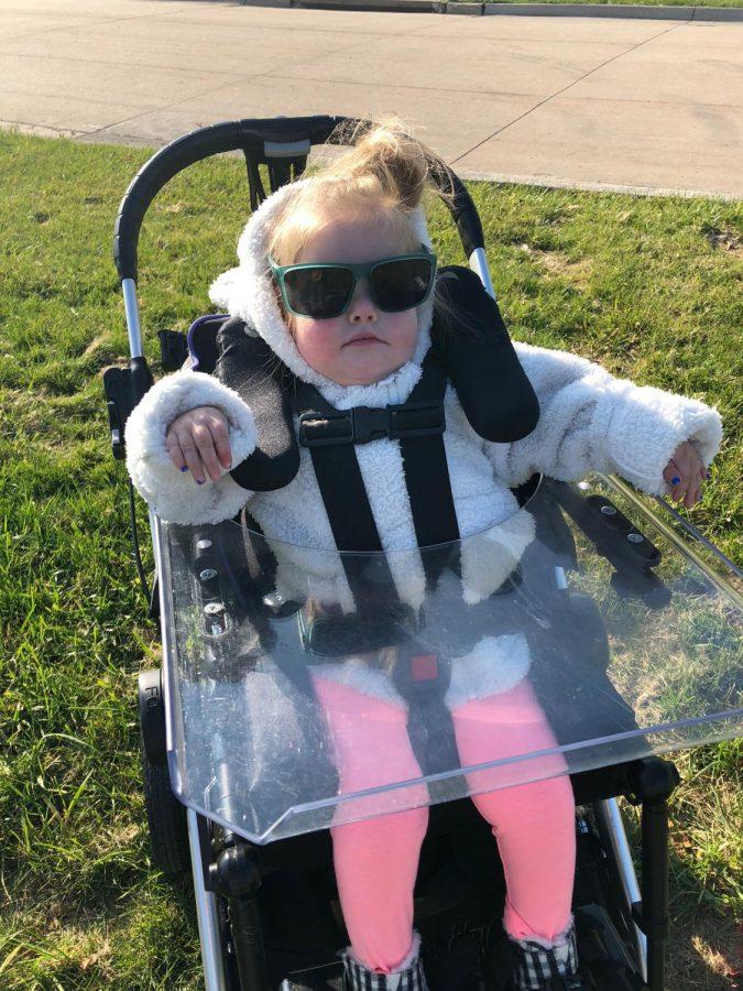 Emilia Emmie Boylan sitting in her adaptive chair while wearing sunglasses.