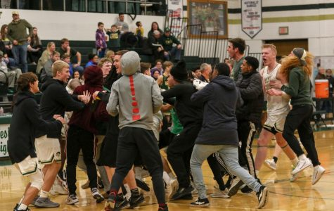 Students and players storm the court after beating Dubuque Hempstead on Jan. 7.