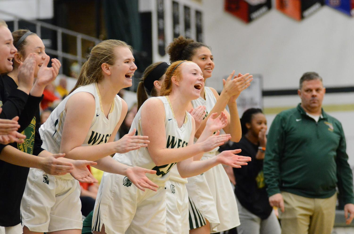 Liv Williams '21, Rylee Goodfellow '21, and Ana Prouty '23 cheer from the bench as Matayia Tellis makes a shot and gets two free throws off of a foul.