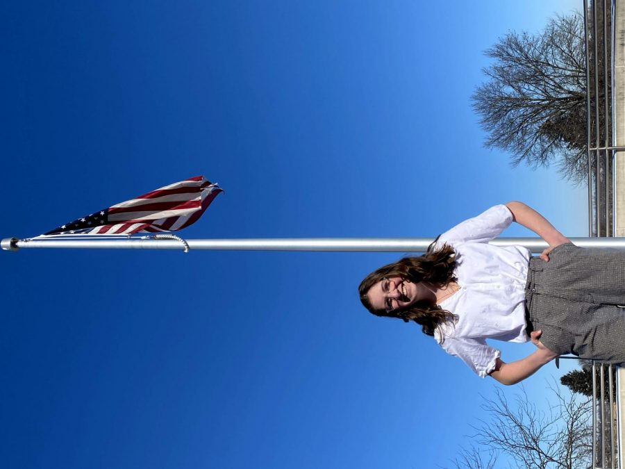 Erica Buettner 21' tells the story of her parents being in the military while posing in front of an american flag