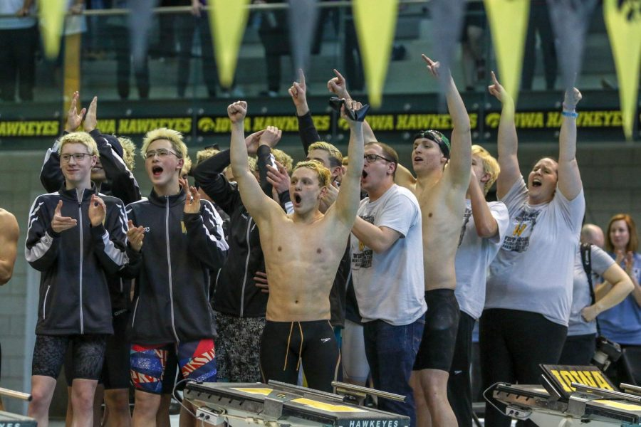 Izaak Hajek 20, along with his teammates and coaches, celebrate as Jordan Christensen 22 recieves his medal on Feb. 15.
