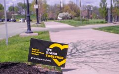 Community members place signs in their yard that say