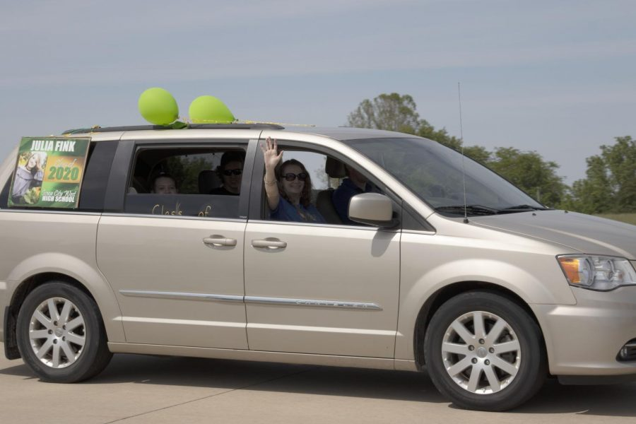Grad Julia Fink and her family wave towards the camera leaving the Coralville Youth Sports Complex.