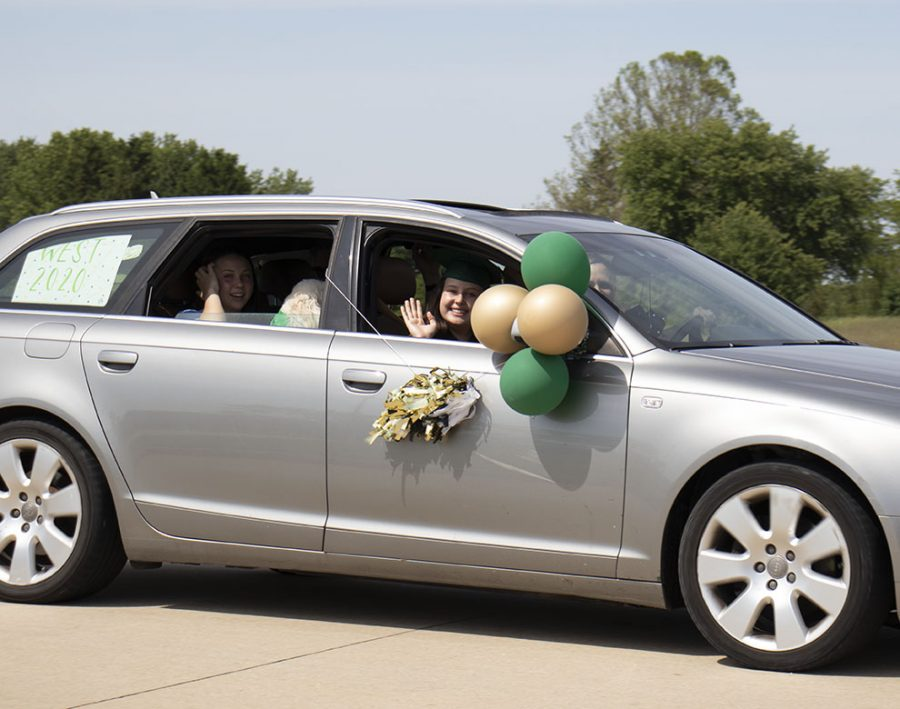 Senior Natalie Dunlap waves to her fellow WSS staffers as she drives past.