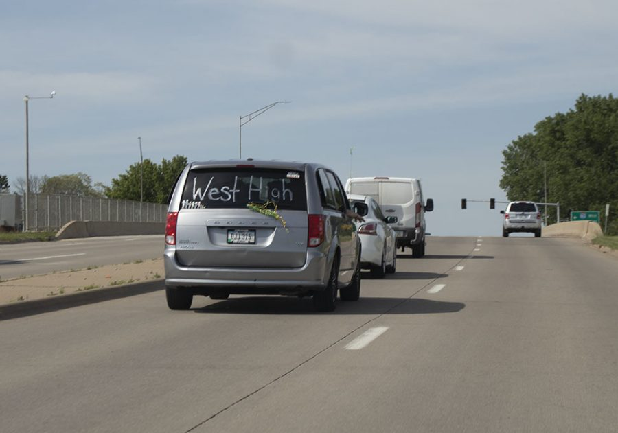 The van shows school pride driving away from the senior car parade.