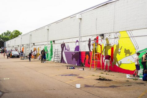 Community members work on a public mural in the South Side district of Iowa City.