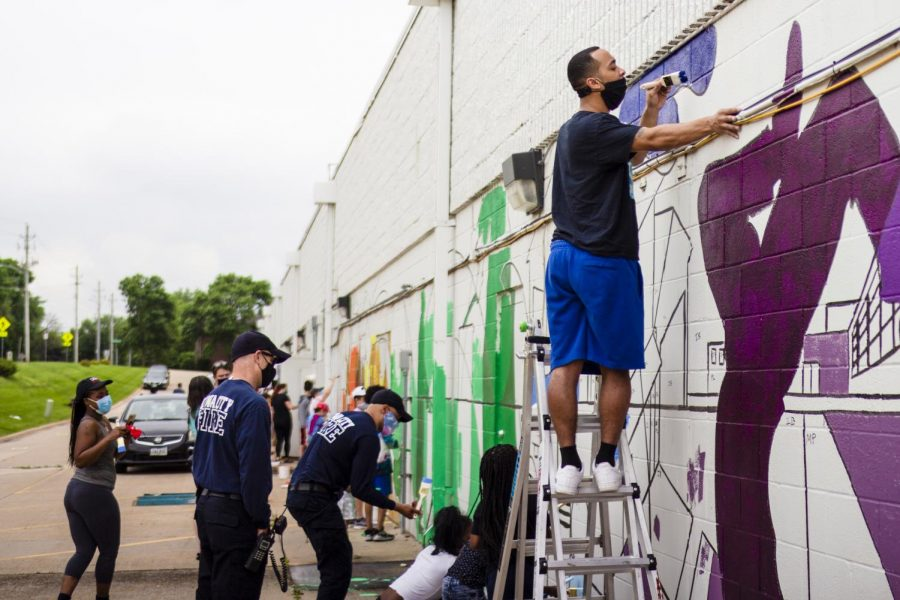 Using a ladder to reacher the higher parts of the mural, painters work together to complete the whole wall.