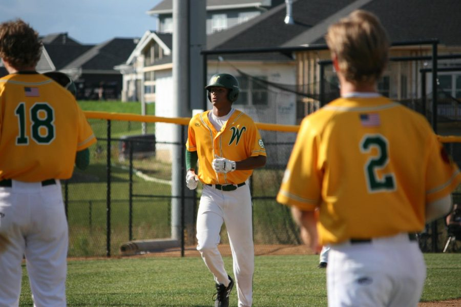 Marcus Morgan '21 returning to home base after hitting a home run as the team rushes to celebrate the play.