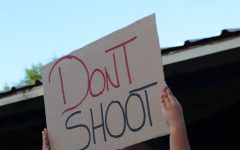 A little girl holds up a sign for the crowd to see, possessing the words 'Don't Shoot.'