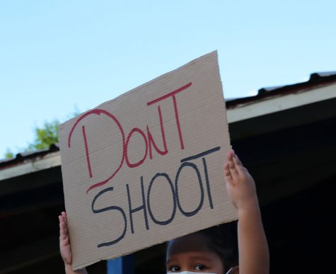 A little girl holds up a sign for the crowd to see, possessing the words