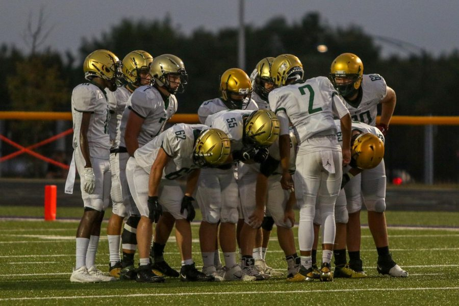 The+offense+huddles+before+their+first+drive+of+the+night+against+Liberty+on+Aug.+28.
