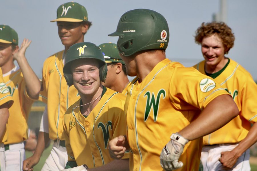 The baseball team celebrates during a summer game.