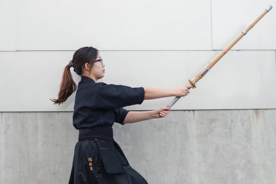 Jimin Seo '22 casts her bamboo sword forward as she stretches her arms to perform her strike.