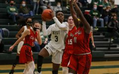 Matayia Tellis '21 goes up for a layup between two City High defenders on Dec. 18.