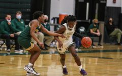 Guard Christian Barnes 22 pushes the ball up the floor past his defender against Kennedy on Feb. 11.