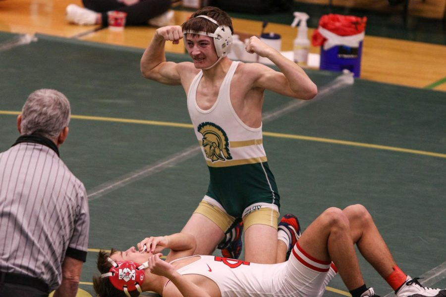 Parker McBride '22 flexes after winning the district championship at 120 pounds on Feb. 13.