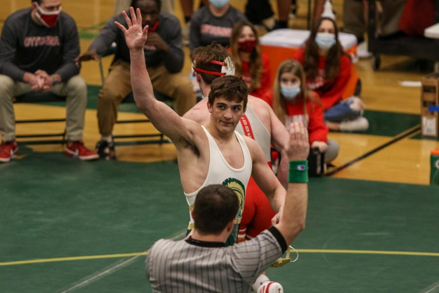 Ashton Barker '21 waves to the fans after defeating Ottumwa's Trevor Summers '22 during the district wrestling meet on Feb. 13.