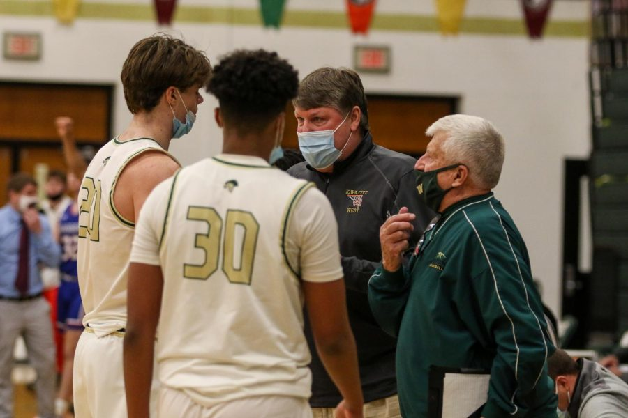 Head coach Steve Bergman talks to Pete Moe '22 during a timeout against Cedar Rapids Washington on Feb. 16.