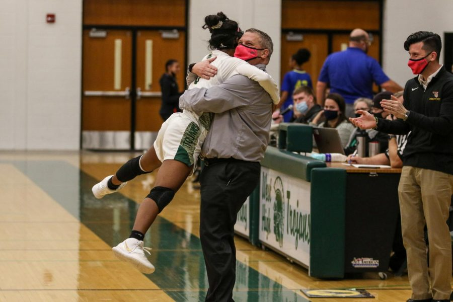 Matayia Tellis '21 hugs head coach BJ Mayer with seconds left in the substate final game on Feb. 23 against Davenport North.