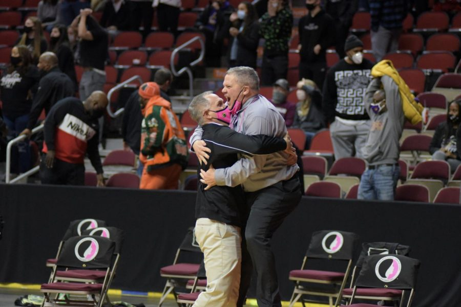 Head coach BJ Mayer jumps into the arms of assistant coach Kris Thorson after the final buzzer celebrating West's win in the 5A state tournament semi-final game March 1.