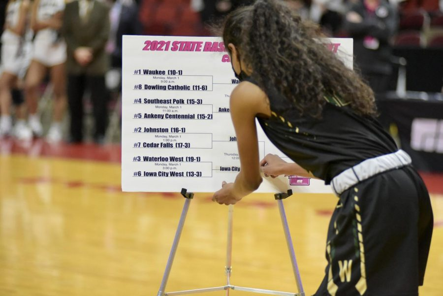 Meena Tate '23 updates the 5A state championship bracket after Iowa City West defeated Waterloo West March 1.