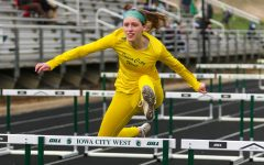 Ella Woods '22 glides over the hurdle while competing in the 100-meter hurdles during the Iowa City West Invitational on March 30.