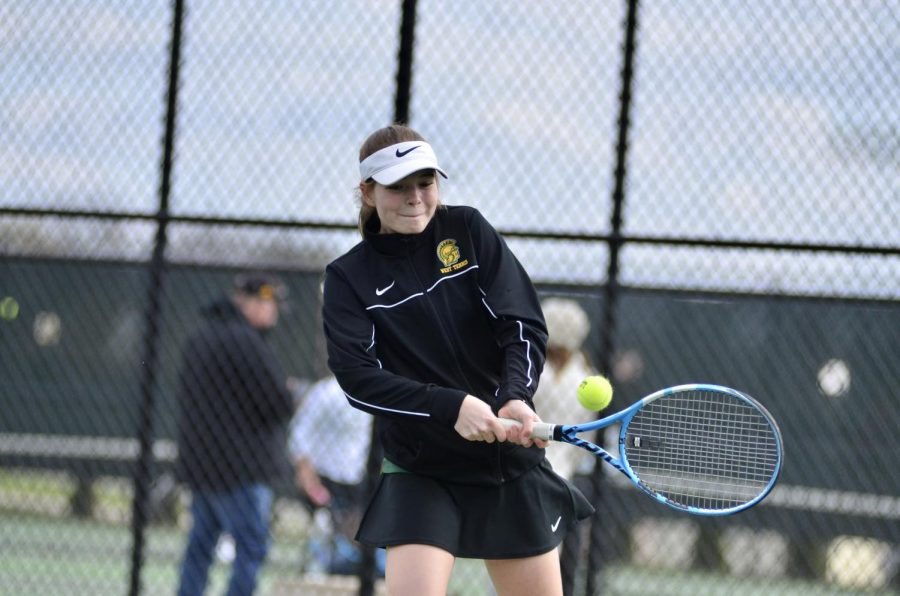 Ella DeYoung '23 returns the ball after her opponents serve April 15.