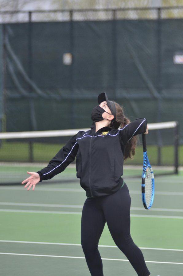 Caroline Chandler '21 focuses on the ball above her to serve April 15 against Prarie.