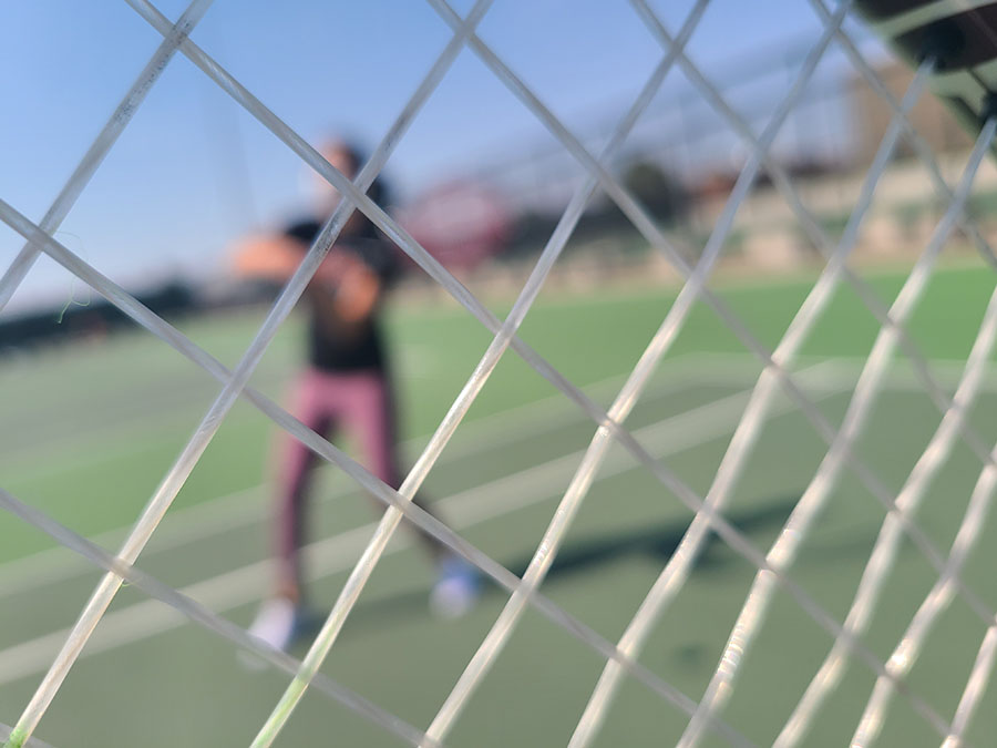 SEEING THROUGH STRINGS  Through the perspective of a tennis racket, Delmira Jara '24 stands in a ready position to volley a soaring tennis ball as it arcs through the sky.