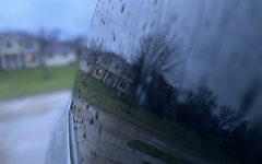 After a huge rainstorm, raindrops chase down a car's window, reflecting a house. Taken in Coralville Iowa after a big rainstorm.
