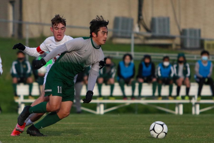 Yulong Shao '21 fights past his defender as he looks to pass ahead against Linn-Mar on April 20 at Ed Barker Field.