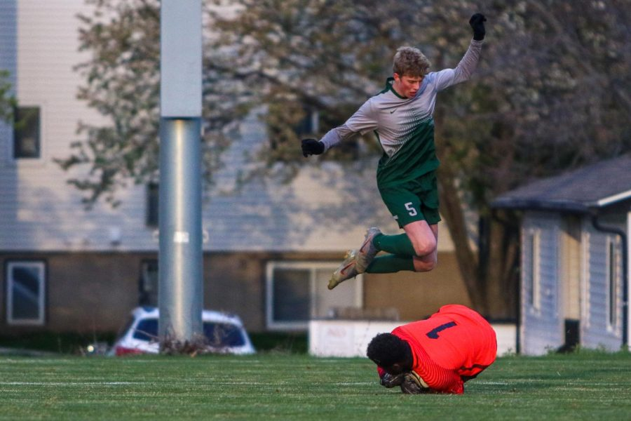 Tyler Johnson '21 leaps over the Linn-Mar keeper after making on April 20 at Ed Barker Field.