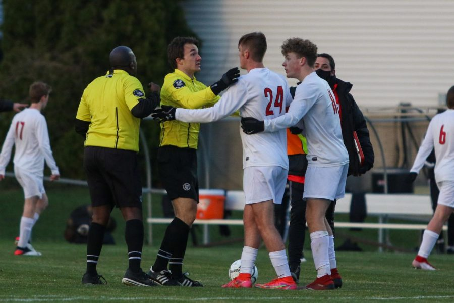 Linn-Mar players and both referees debate a call at the end of the first half on April 20 at Ed Barker Field.