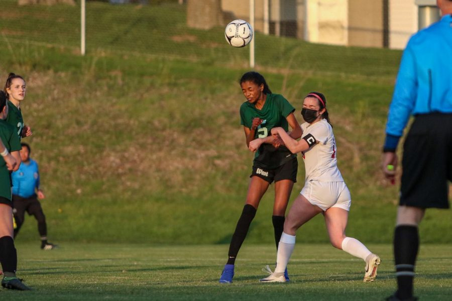 Meena Tate '22 heads the ball into the penalty box against City High at Ed Barker Field on April 22.