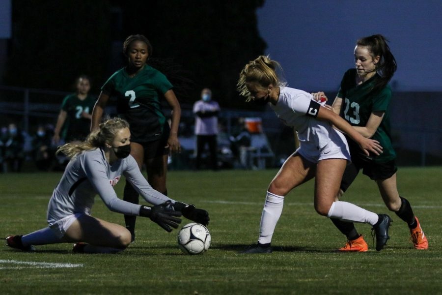 Kenadee Showalter '22 fights for a chance at the ball against City High at Ed Barker Field on April 22.