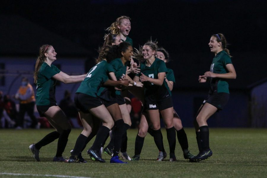Meena Tate '23 is swarmed by her teammates as they celebrate her goal to put the Trojans up 1-0 against City High at Ed Barker Field on April 22.